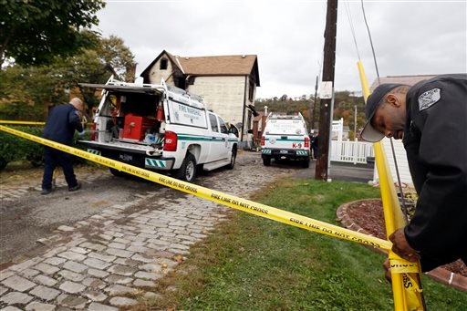 A McKeesport police officer, right, ties fire tape around the scene of the house in McKeesport, Pa., where a fire killed six members of a family, four of them children, and left another in the hospital in critical condition, on Saturday, Oct. 18, 2014.