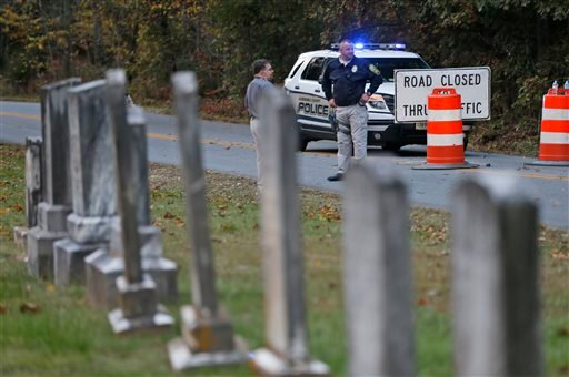 Police block the road leading to the scene of a death investigation in connection with the disappearance of University of Virginia student Hannah Graham in Albermarle County, Va., Saturday, Oct. 18, 2014. (AP Photo/Steve Helber)