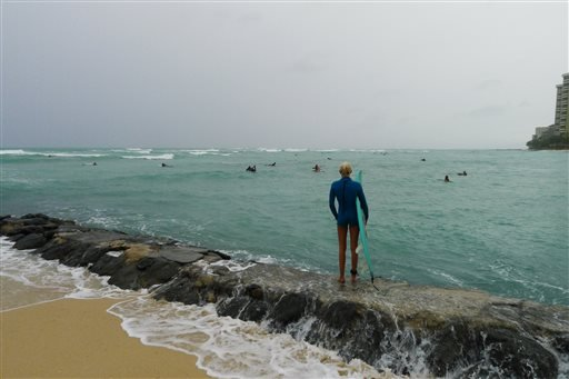 Surfer Emile Meder, 23 of Honolulu, watches the waves at Waikiki Beach in Honolulu, Hawaii on Sat., Oct. 18, 2014 as Hurricane Ana passes southwest of Hawaii. (AP Photo/Cathy Bussewitz)