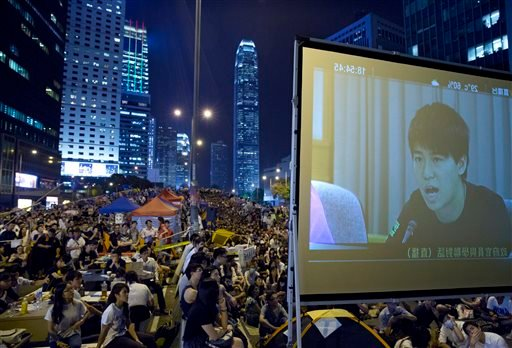 Pro-democracy protesters watch a live TV showing talks between Hong Kong government officials and students at an occupied area outside the government headquarters in Hong Kong's Admiralty district,Tuesday, Oct. 21, 2014.