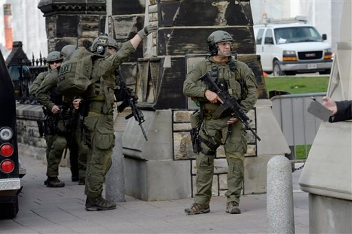 A Royal Canadian Mounted Police intervention team walks past a gate on Parliament hill in Ottawa Wednesday Oct. 22, 2014. (AP Photo/The Canadian Press, Adrian Wyld)