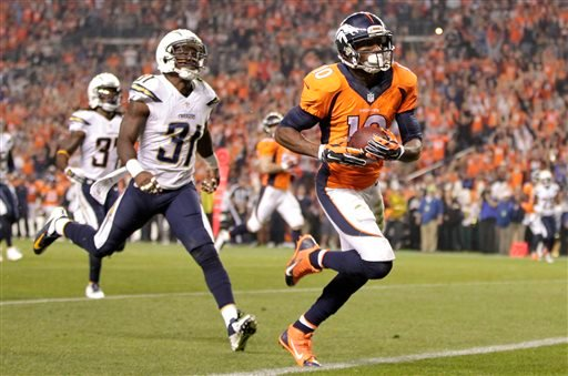 Denver Broncos wide receiver Emmanuel Sanders (10) scores his second touchdown of the NFL football game, as San Diego Chargers cornerback Richard Marshall (31) defends during the first half Thursday, Oct. 23, 2014, in Denver. (AP Photo/Joe Mahoney)
