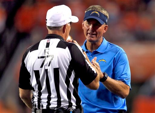 San Diego Chargers coach Mike McCoy talks with referee Terry McAulay (77) during the second half of an NFL football game against the Denver Broncos, Thursday, Oct. 23, 2014, in Denver. (AP Photo/Joe Mahoney)