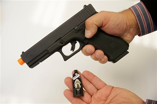 In this photo taken Wednesday, Oct. 22, 2014, Jim Schaff, vice president of marketing with Yardarm, holds a sensor that fits into an Airsoft replica of a Glock 17 handgun in San Francisco.