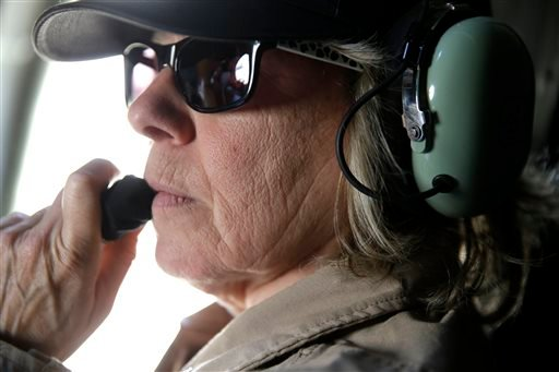 Crew member Caren Landis talks to other crew members as the B-29 bomber they are flying turns to final for landing enroute from Baton Rouge, La., to New Orleans, Thursday, Oct. 23, 2014.