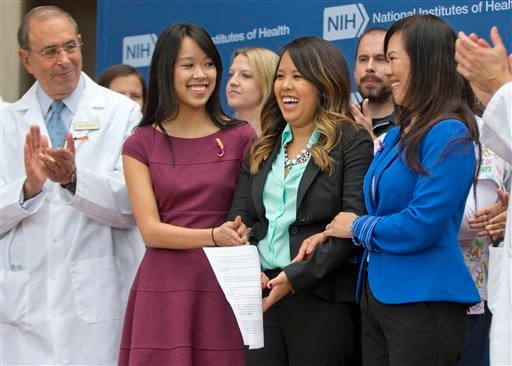 Patient Nina Pham, center, with her mother Diana Berry, right, and sister Cathy Pham, left, smiles as members of the NIH staff outside applaud during a news conference at NIH in Bethesda, Md., Friday, Oct. 24, 2014.