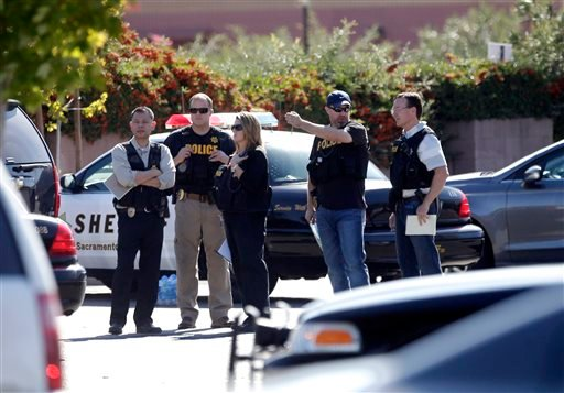 Law enforcement officers gather at the site where a Sacramento County Sheriff's deputy was shot by an assailant who then carjacked two vehicles prompting a manhunt in Sacramento, Calif., Friday, Oct. 24, 2014. (AP)