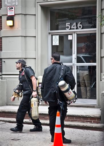 Bio recovery workers carry air tanks as they arrive at the apartment of Dr. Craig Spencer Friday Oct. 24, 2014 in New York.