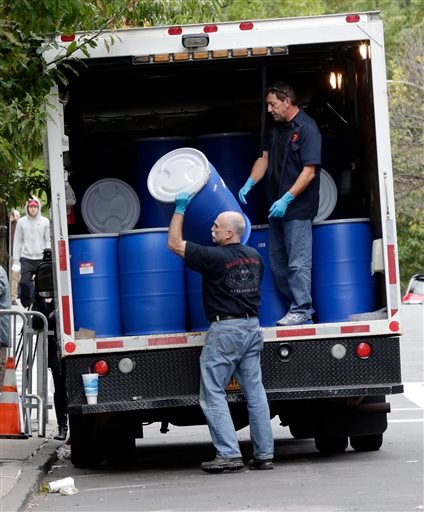 Workers from BioRecoveryCorp unload barrels at the apartment building of Ebola patient Dr. Craig Spencer, in New York, Friday, Oct. 24, 2014.