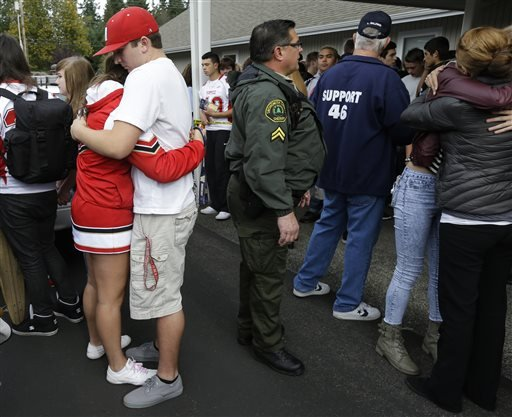 Students comfort each other at left at a church Friday, Oct. 24, 2014, where students were taken to reunite with parents following a shooting at Marysville Pilchuck High School in Marysville, Wash. (AP Photo/Ted S. Warren)