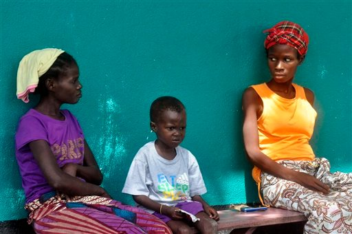 In this photo taken on Friday, Oct. 24, 2014, three people suspected of having contracted the Ebola virus await treatment outside a hospital inthe Bomi County area, near Monrovia, Liberia.