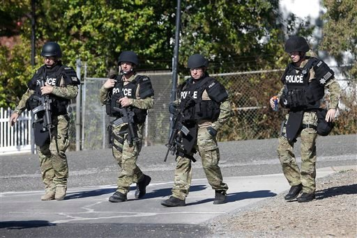 Law enforcement officers dressed in tactical gear leave the Gold County Fairgrounds to help in the search of an assailant, in Auburn, Calif., who shot three sheriff's deputies in two Northern California Counties, Friday, Oct. 24, 2014.