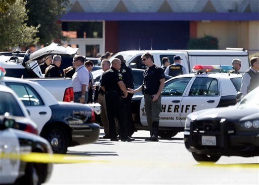 Law enforcement officers gather at the site where a Sacramento County Sheriff's deputy was shot by an assailant who then carjacked two vehicles prompting a manhunt in Sacramento, Calif., Friday, Oct. 24, 2014.