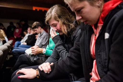 Friends comfort each other as hundreds packed into The Grove Church for a vigil in mourning of an earlier shooting at Marysville Pilchuck High School that left two dead and four wounded Friday, October 24, 2014, in Marysville, Washington.