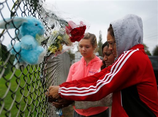 Marysville Pilchuck student Tyanna Davis, right, places flowers on the fence bordering Marysville Pilchuck High School in Marysville, Wash., Saturday, Oct. 25, 2014.