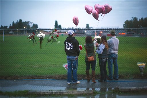 A memorial grows Saturday Oct. 25, 2014 at the entrance to Marysville Pilchuck High School the day after a shooting in the school cafeteria left two dead and four wounded.
