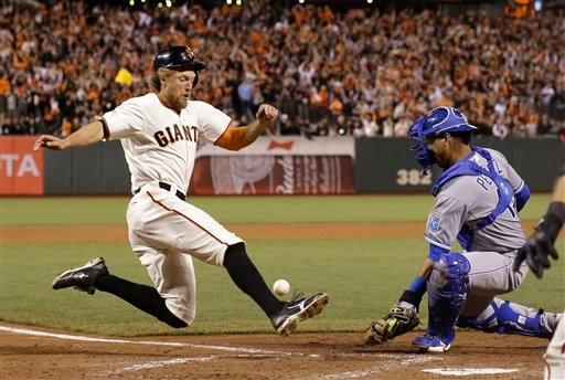 Kansas City Royals Salvador Perez misses the throw to home as San Francisco Giants Hunter Pence scores on a two-run RBI double by Juan Perez during the eighth inning of Game 5 of baseball's World Series Sunday, Oct. 26, 2014, in San Francisco.