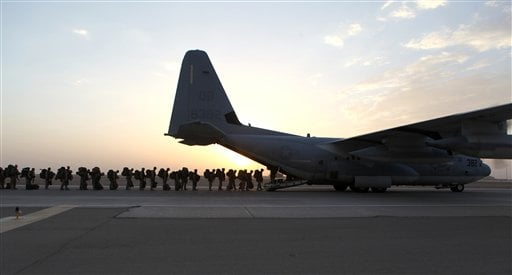 This handout photo provided Defense Department shows Marines and sailors with Marine Expeditionary Brigade – Afghanistan load onto a KC-130 aircraft on the Camp Bastion, Afghanistan flightline, Monday, Oct. 27, 2014. (AP)
