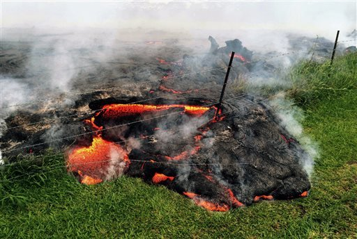 This Oct. 25, 2014 photo provided by the U.S. Geological Survey shows lava flow advancing across the pasture between the Pahoa cemetery and Apaa Street, engulfing a barbed wire fence, near the town of Pahoa on the Big Island of Hawaii.
