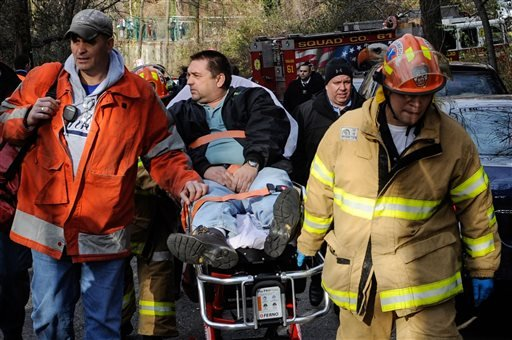 In this Dec. 1, 2013 file photo, Metro North Railroad engineer William Rockefeller is wheeled on a stretcher away from the area where the commuter train he was operating derailed in the Bronx borough of New York.