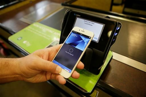 In this photo taken Friday, Oct. 17, 2014, Eddy Cue, Apple Senior Vice President of Internet Software and Services, demonstrates the new Apple Pay mobile payment system at a Whole Foods store in Cupertino, Calif.