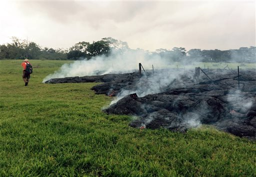This Oct. 26, 2014 photo provided by the U.S. Geological Survey a Hawaii Volcano Observatory geologist mapping the margin of the June 27 lava flow in the open field below Cemetery Road near the town of Pahoa on the Big Island of Hawaii. (AP)