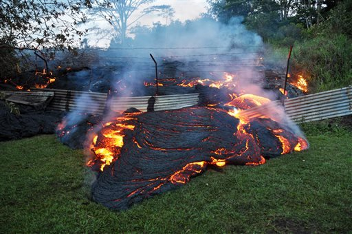This Tuesday, Oct. 28, 2014 photo provided by the U.S. Geological Survey shows lava that has pushed through a fence marking a property boundary above the town of Pahoa on the Big Island of Hawaii. (AP Photo/U.S. Geological Survey)