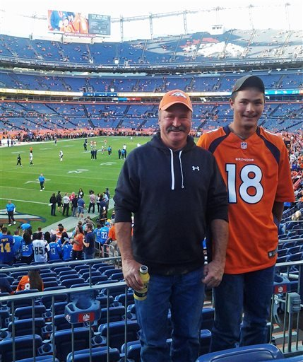In this Oct. 23, 2014 photo provided by Jarod Tonneson, Paul Kitterman, left, and his stepson Jarod Tonneson pose for a photo during a San Diego Chargers-Denver Broncos football game at Sports Authority Field in Denver.