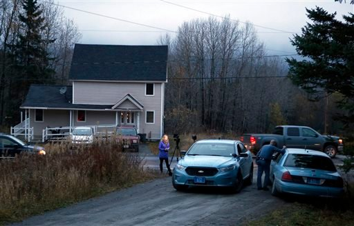State troopers and a television reporter stand across from the home where Kaci Hickox, a nurse who treated Ebola patients in West Africa, is staying Oct. 29, 2014, in Fort Kent, Maine. (AP Photo/Robert F. Bukaty)