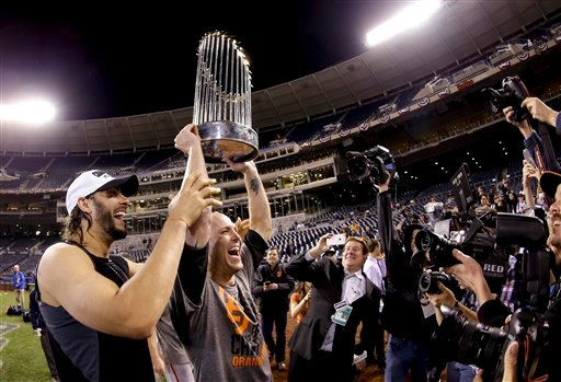 San Francisco Giants left fielder Michael Morse, left, and starting pitcher Tim Hudson holds up the trophy after their win in Game 7 of baseball's World Series against the Kansas City Royals Wednesday, Oct. 29, 2014, in Kansas City, Mo. (AP Photo/Charlie