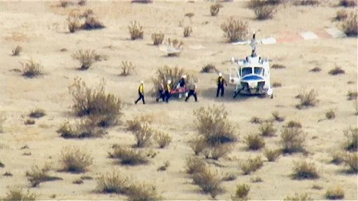 In this image from video by KABC-TV Los Angeles, a rescue crew carries a person on a stretcher to a waiting helicopter near the scene of a crash of the SpaceShipTwo in Southern California's Mojave Desert on Friday, Oct. 31, 2014.