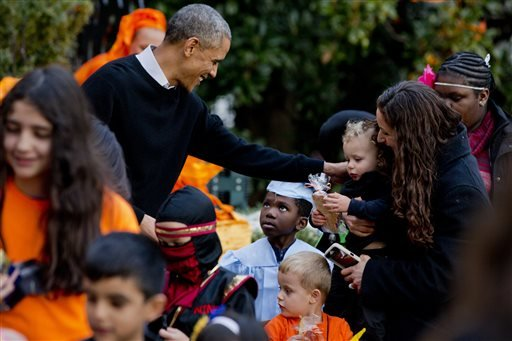 A boy dressed as a college graduate looks up at President Barack Obama as the president greets costumed trick-or-treaters during Halloween festivities by the South Portico of the White House in Washington, Friday, Oct. 31, 2014. (AP)