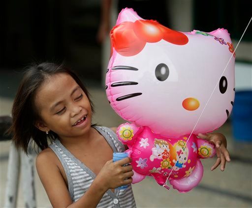 In this Friday, Oct. 17, 2014 photo, a girl admires a Hello Kitty balloon sold in Manila, Philippines. (AP)