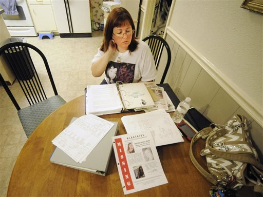Oct. 21, 2014 photo: Stephanie Hanke, stepmother of missing teenager Brittney Wood, looks over materials related to the search for the youth at her home in Mobile, Ala. (AP Photo/Jay Reeves)