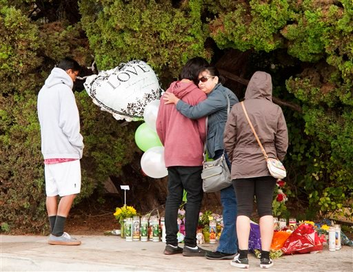 Mourners gather at the street-side memorial at North Jacaranda Street and Fairhaven Avenue in Santa Ana, Calif. on Saturday, Nov. 1, 2014 for three teenage trick-or-treaters killed in a Friday night hit-and-run accident. (AP Photo/Orange County Register,