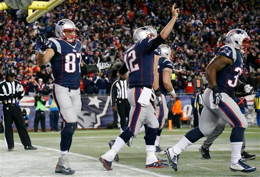 Patriots tight end Rob Gronkowski, left, reacts after catching a touchdown pass from quarterback Tom Brady, celebrating at center, in the second half of an NFL football game against the Broncos Nov. 2, 2014, in Foxborough. (AP Photo/Elise Amendola)