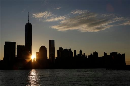 The sun rises next to One World Trade Center, Monday, Nov. 3, 2014 in this view from Jersey City, N.J.  (AP Photo/Mark Lennihan)