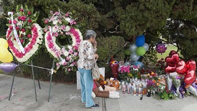 A woman visits the street-side memorial at North Jacaranda Street and Fairhaven Avenue in Santa Ana Nov. 1, 2014 for three teenage trick-or-treaters killed in a Friday night hit-and-run accident. (AP Photo/Orange County Register, Ken Steinhardt)