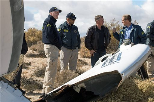 In this Nov. 1, 2014, photo provided by the National Transportation Safety Board, Virgin Galactic pilot Todd Ericson, right, talks with NTSB Acting Chairman Christopher A. Hart, second from left, at the SpaceShipTwo accident site. (AP)