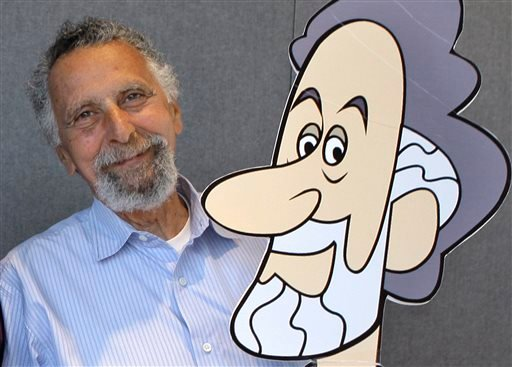 """In this June 19, 2008 photo, Tom Magliozzi, co-host with his brother Ray of National Public Radio's """"Car Talk"""" show, poses with a caricature of himself in Cambridge, Mass. (AP)"""