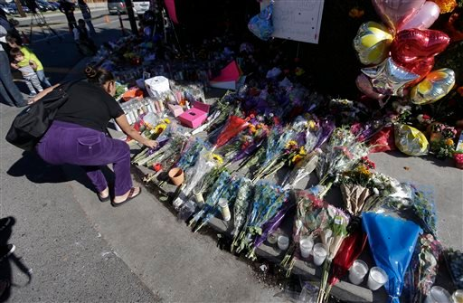 A well-wisher places flowers at a makeshift memorial near where three teenagers were killed in a hit and run accident on Halloween, Monday, Nov. 3, 2014, in Santa Ana, Calif. (AP Photo/Chris Carlson)