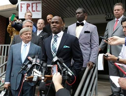 Minnesota Vikings running back Adrian Peterson, center, and his attorney Rusty Hardin, left, speak to the media after pleading no contest to an assault charge Tuesday, Nov. 4, 2014, in Conroe, Texas.