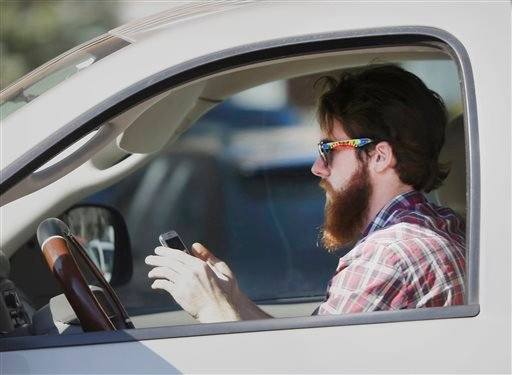 FILE - In this Feb. 26, 2013 file photo, a man uses his cell phone as he drives through traffic in Dallas. (AP)