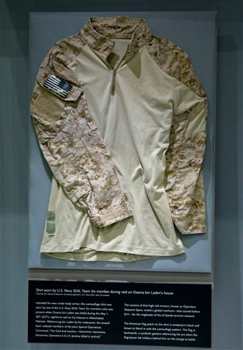 This Sept. 5, 2014 file photo provided by the National September 11 Memorial and Museum, shows the fatigue shirt worn by Navy SEAL Robert O'Neill during the mission to capture Osama bin Laden, in a case at the museum in New York.