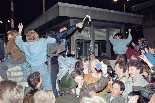 In this Nov. 10, 1989, file photo, East and West Berliners mingle as they celebrate in front of a control station on East Berlin territory.