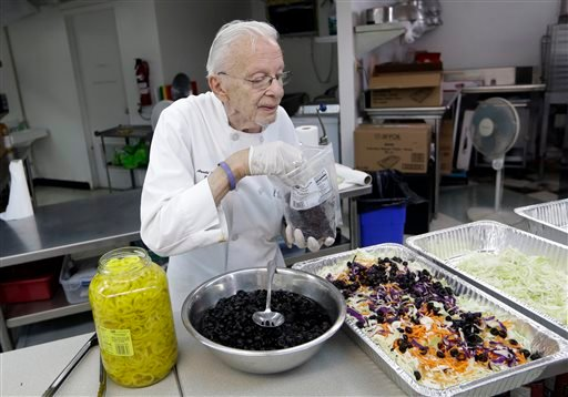 Homeless advocate Arnold Abbott, 90, director of the nonprofit group Love Thy Neighbor Inc., prepares a salad in the kitchen of The Sanctuary Church, Wednesday, Nov. 5, 2014, in Fort Lauderdale, Fla.