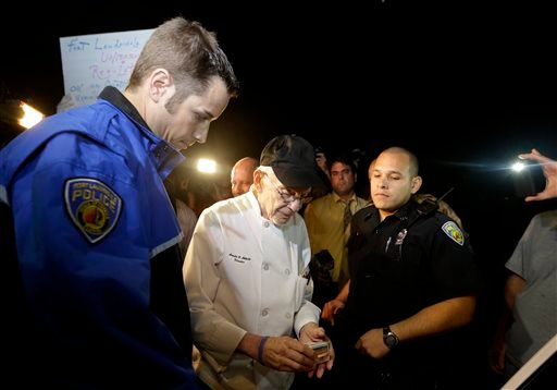 Homeless advocate Arnold Abbott, 90, of the nonprofit group Love Thy Neighbor Inc., center, gets his drivers license to hand to a Fort Lauderdale police officer, Wednesday, Nov. 5, 2014, in Fort Lauderdale, Fla.