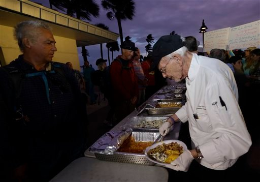 Homeless advocate Arnold Abbott, 90, director of the nonprofit group Love Thy Neighbor Inc., right, serves food to the homeless from a public parking lot next to the beach, Wednesday, Nov. 5, 2014, in Fort Lauderdale, Fla.
