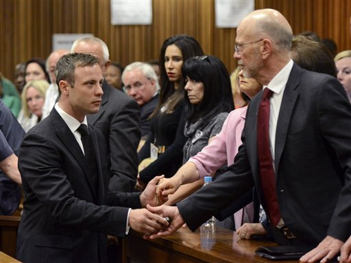 In this Oct. 21, 2014, file photo, Oscar Pistorius, left, greets his uncle Arnold Pistorius, right, and other family members as he is led down to the cells of the court in Pretoria. (AP Photo/Herman Verwey, Pool, File)