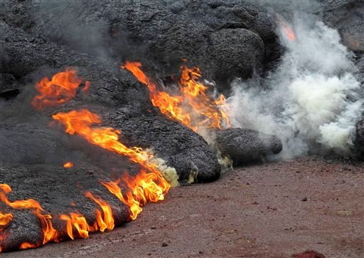 This Nov. 9, 2014 photo provided by the U.S. Geological Survey shows the lava flow from the Kilauea Volcano that began on June 27 as it burns along Cemetery Road and Apa?a Street near the town of Pahoa on the Big Island of Hawaii. (AP)